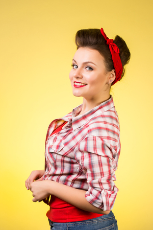 Beautiful young woman with pin-up make-up and hairstyle posing over pink background. Stock Photo