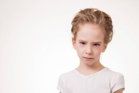 frowns: Cute teen girl angry frowns, studio portrait isolated on white background.