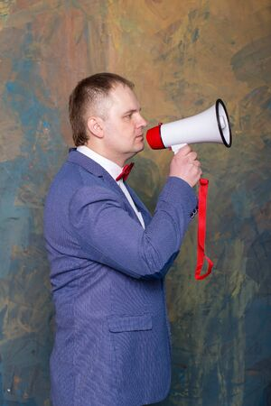 businessman using a megaphone: angry businessman using megaphone over grey background