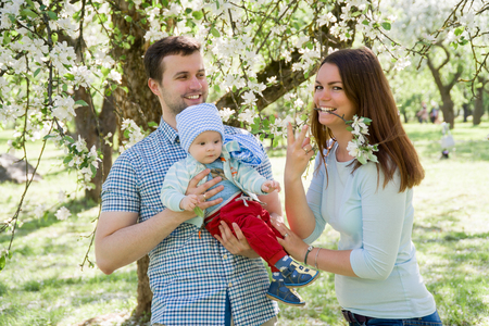 young happy family walking outdoor. Parents hold child on hands and rejoice. They are happy together. Smile each other