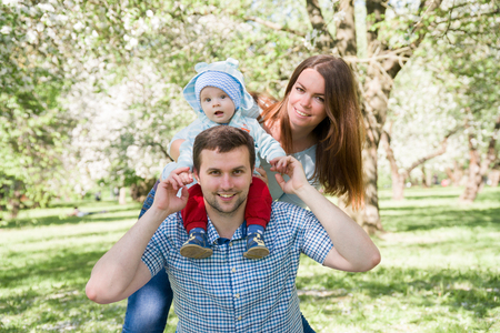 Young happy family walking outdoor. Parents hold child on hands. Stockfoto