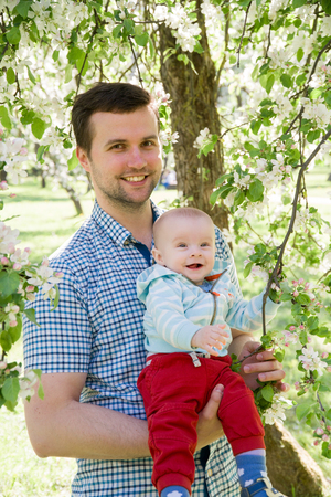 young happy family walking outdoor. Father hold child on hands and rejoice. They are happy together. Smile each other. Stockfoto