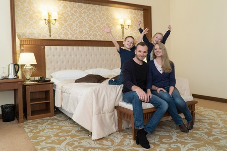 a happy family posing on camera in hotel room sitting on bed Stok Fotoğraf