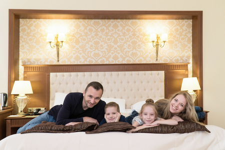 a happy family posing on camera in hotel room sitting on bed Stockfoto