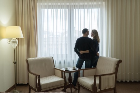 The newlyweds stand at the window of the hotel room and look at each other. Young family is very happy Stok Fotoğraf