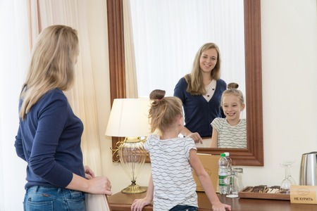 A young mother and daughter are standing in front of a mirror in a hotel room and smiling. Family is very happy