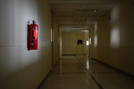 fire extinguisher: Fire extinguisher in dimly lit corridor