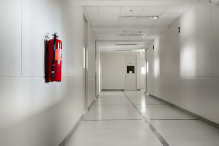 Fire extinguisher in empty corridor Stock Photo