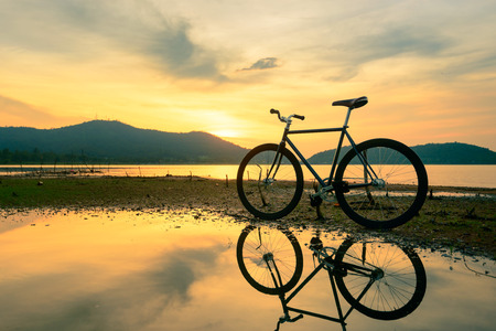 Bicycle parked near a lake with reflection