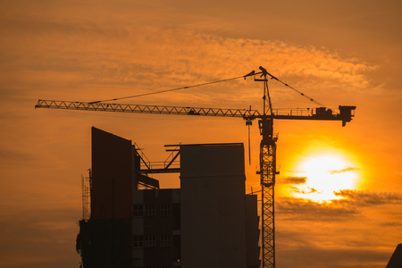 building site: Industrial construction crane on sunset in a building site Stock Photo