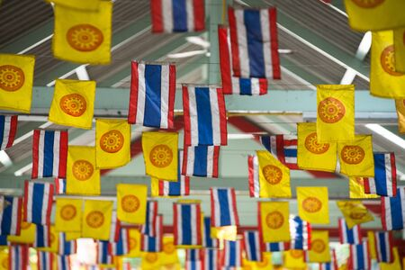 Thai national flag and dharmachakra flag decorated above a walking street photo