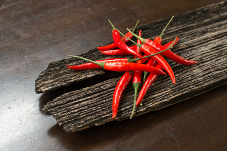 thai chili pepper: Red chillies on a plank on a table Stock Photo