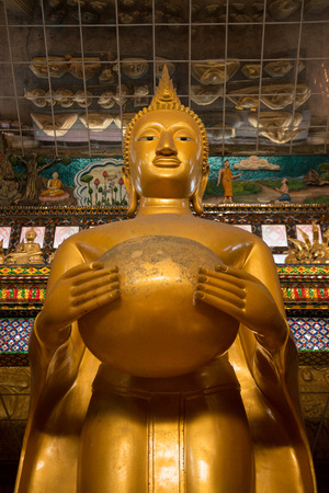 alms: Big golden buddha statue holding an alms bowl Editorial