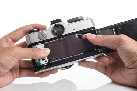 vintage camera: Hands loading film into SLR camera