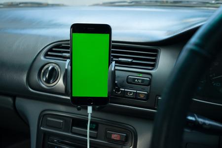 一般的な車のダッシュ ボードの緑色の画面を持つスマート フォン