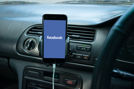 handsfree telephone: BANGKOK, THAILAND - OCTOBER 30, 2015: Smartphone mounted on a generic cars dashboard with social media on its screen. Editorial