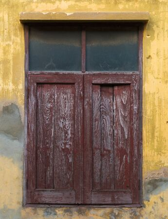 Old wooden window on yellow weathered wall Фото со стока
