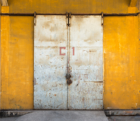 Locked metal grunge metal door on yellow wall