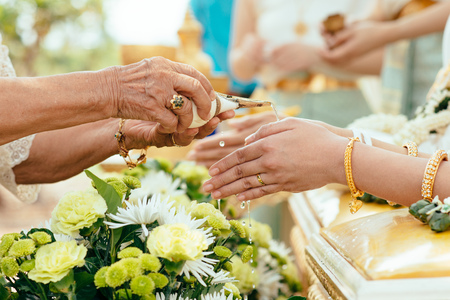 Elder pours ceremonial water into the brides hand in a Thai traditional wedding ceremony Фото со стока