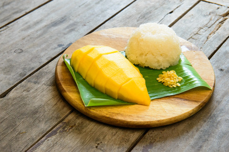 Mango sticky rice  on wooden plate Фото со стока