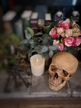 Halloween still life : The human skull with white candle light, vintage key chain, bottle, books,  flower bouquet in vase and ornamental plants on wooden table in the room