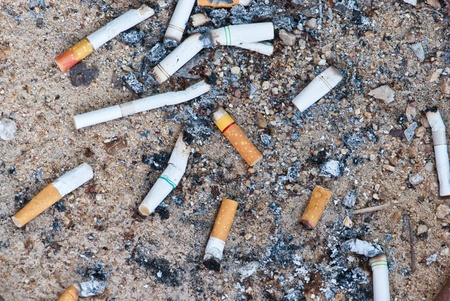 Lots of cigarette buds on sandy background Stock Photo - 10657339