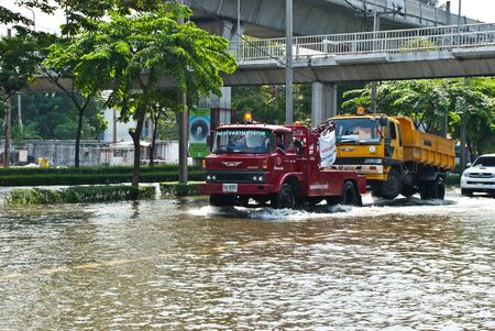 BANGKOK - NOVEMBER 7 2011: Heavy truck is toed by service truck after impact with heaviest flood and rain in 20 years in the capital on November 07, 2011 in Bangkok, Thailand. Stock Photo - 11215785