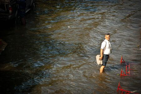 waited: BANGKOK - NOVEMBER 7 2011: A man waited for free transport after impact with heaviest flood and rain in 20 years in the capital on November 07, 2011 in Bangkok, Thailand.
