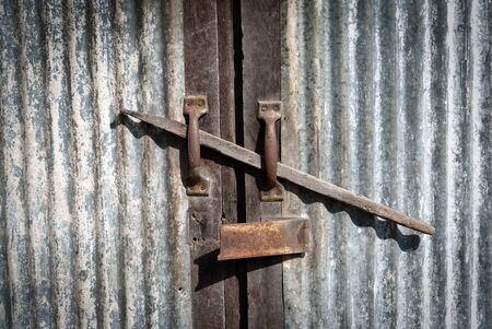 Old metal lock and metal door with wooden pole in the middle. Stock Photo - 11308910
