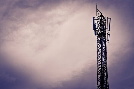Mobile communication antenna taken on a cloudy day with silhouette photo
