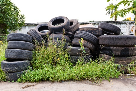 Old road tires stacked on grass land as background