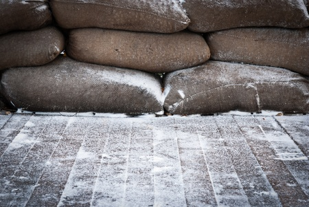 Old brown sandbags on snow covered wooden floor, taken on a winter morning. photo