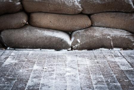 Vieux sacs de sable brun recouvert de neige sur plancher de bois, prise un matin d'hiver.