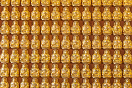 Hundreds of golden Buddha statues background at chinese temple photo