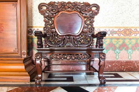 Old large wooden polished chinese chair with brown patterns photo