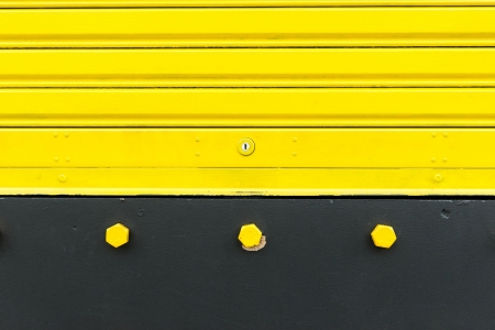 Bright yellow metal sliding door with key hole, taken on a cloudy day. Stock Photo - 16439088