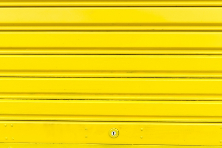 Bright yellow metal sliding door with key hole, taken on a cloudy day. photo