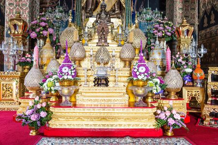 Tradtional buddha golden praying set complete with flowers, taken indoor in public temple Editorial