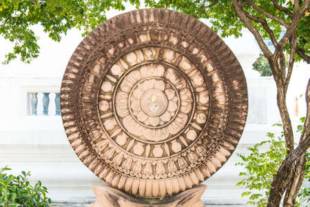 Close up of a wheel of Buddha made from lime stone, taken on a sunny day