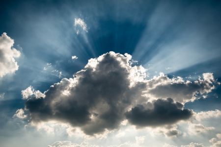 A storm grey cloud blocking the sun, giving the ray of light at the background Stock Photo - 18682894