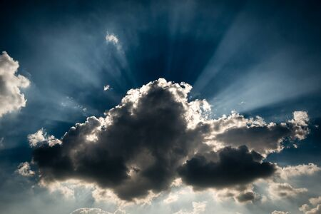 A storm grey cloud blocking the sun, giving the ray of light at the background Stock Photo - 18682899