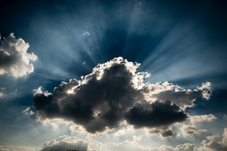 A storm grey cloud blocking the sun, giving the ray of light at the background Stock Photo - 18682898