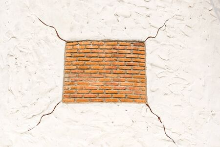 taken: Red square shape brick on white background with cracks, taken outdoor. Stock Photo