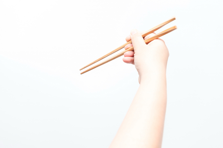 chop stick: Asian woman holding brown chop stick, isolated Stock Photo
