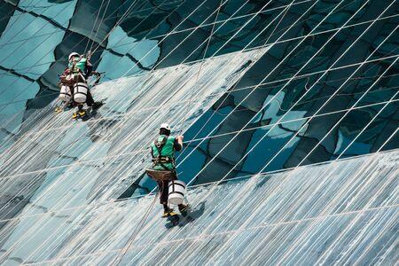 Groupe de nettoyage des vitres, le nettoyage d'un immeuble de bureaux de grande hauteur sur une journée ensoleillée