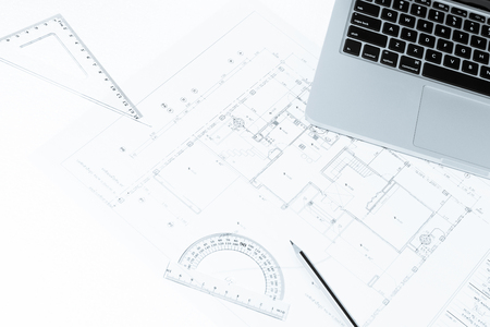 Pen, drawing rulers, and notebook over house construction blueprint with blue tone effect, useful for construction, business, architecture, engineering, insurance background concepts Stock Photo