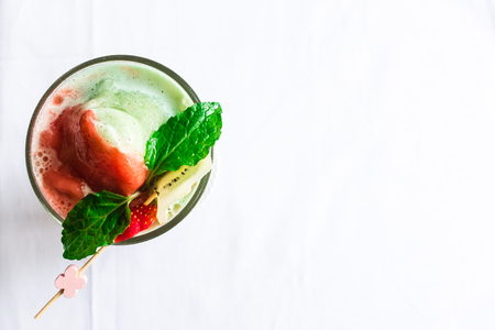 Topdown view of strawberry, banana, giwi smoothy glass with green leaf, taken outdoor with natural lights Stock Photo
