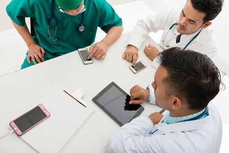 Asian male and female doctor and nurse on table looking at smart devices with white background, useful for digital health care, digital medical care, ehospital, e-medication concepts