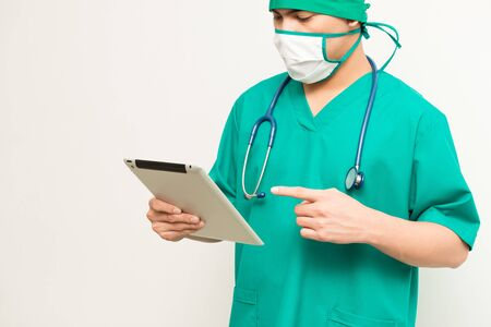 Asian male medical doctor using tablet on white background, useful for medical, hospital, medication, surgent, medical advise, doctor, health care concepts