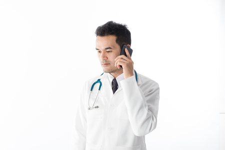 Asian male medical doctor using smart phone on white background, useful for medical, hospital, medication, surgent, medical advise, doctor, health care concepts